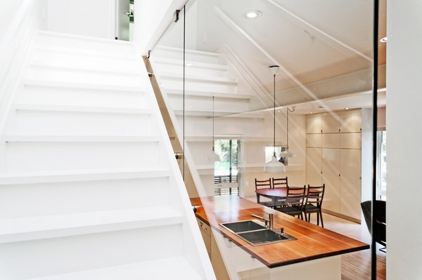 Modern home with wood tread, glass railing, bar, light hardwood floor, ceiling lighting, kitchen, wood counter, and white cabinet. Our House - Staircase Photo 14 of Our House