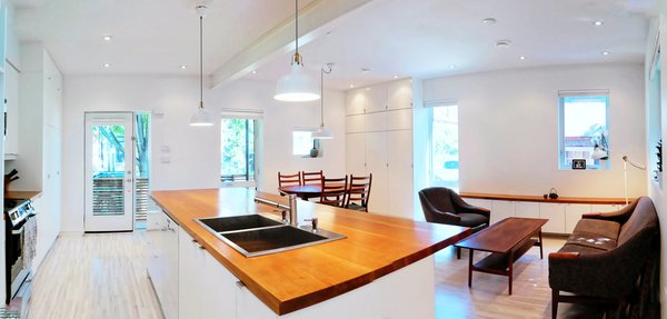 Modern home with sofa, coffee tables, ceiling lighting, accent lighting, light hardwood floor, pendant lighting, bar, storage, table, chair, and living room. Our House - Great Room Photo 9 of Our House