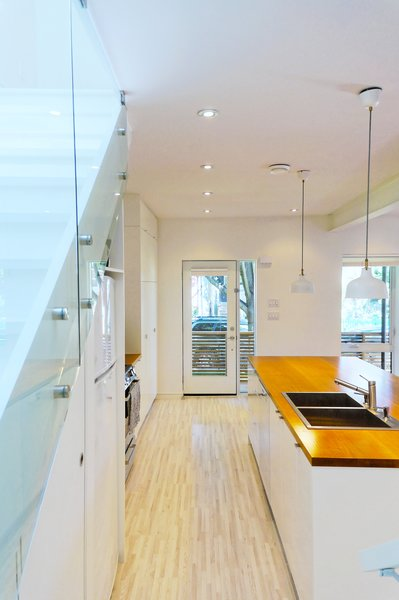 Modern home with wood counter, drop in sink, white cabinet, light hardwood floor, ceiling lighting, pendant lighting, staircase, and glass railing. Our House - Kitchen Photo 11 of Our House