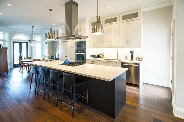Modern home with kitchen, dark hardwood floor, stone counter, white cabinet, ceiling lighting, pendant lighting, range hood, range, microwave, wall oven, and cooktops. Bickford Park - Kitchen Photo 12 of Bickford Park
