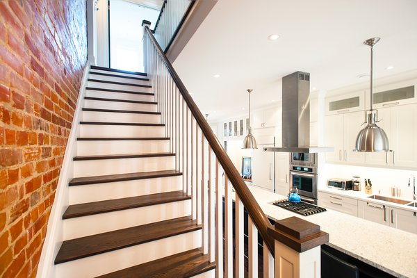 Modern home with stone counter, white cabinet, pendant lighting, ceiling lighting, accent lighting, range hood, cooktops, staircase, wood tread, and wood railing. Bickford Park - Stairs Photo 9 of Bickford Park