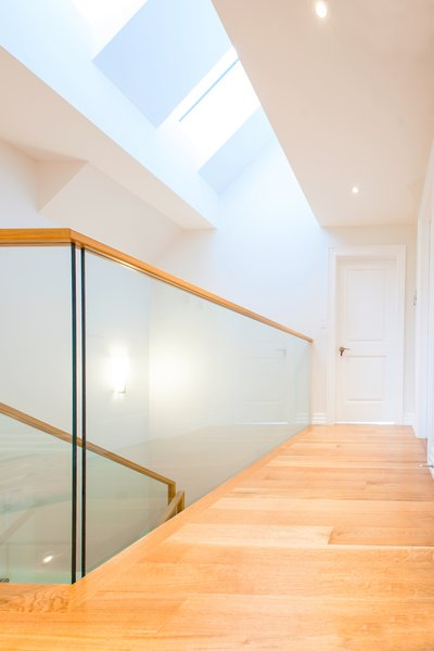 Modern home with glass railing, hallway, and medium hardwood floor. Edwardian Renovation - Third Floor Hallway Photo 6 of Edwardian Renovation