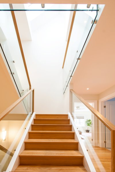 Modern home with wood tread, glass railing, hallway, and medium hardwood floor. Edwardian Renovation - Stairs Photo 7 of Edwardian Renovation