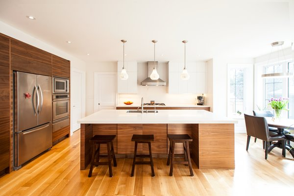 Modern home with bar, stools, accent lighting, ceiling lighting, pendant lighting, medium hardwood floor, kitchen, white cabinet, refrigerator, and undermount sink. Edwardian Renovation - Kitchen Photo 10 of Edwardian Renovation