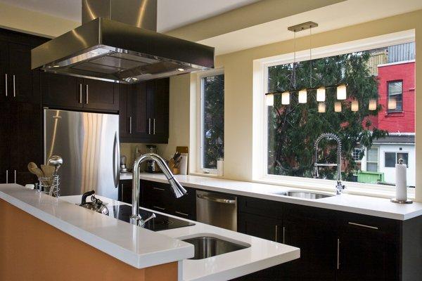 Modern home with kitchen, wood cabinet, pendant lighting, accent lighting, range hood, refrigerator, and undermount sink. Laneway Loft - Kitchen Photo 9 of Laneway Loft