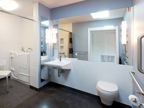 Modern home with bath room, ceiling lighting, wall lighting, one piece toilet, and wall mount sink. Roncesvalles Accessible House - Master Bathroom Photo 4 of Roncesvalles Accessible House