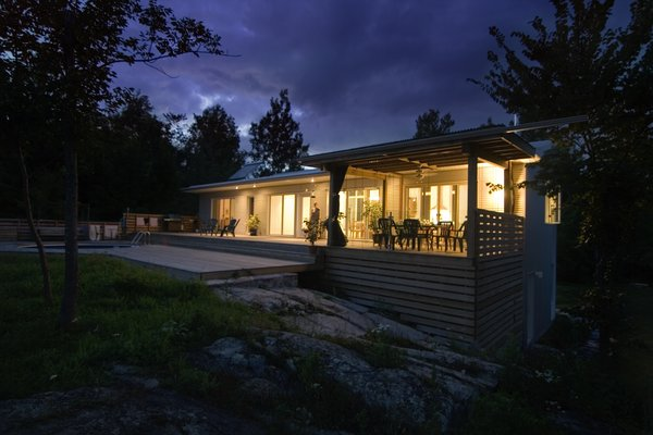 Modern home with outdoor, large patio, porch, deck, stone patio, porch, deck, wood patio, porch, deck, horizontal fence, and wood fence. Gananoque Lake Road House - Second Floor Exterior Photo 5 of Gananoque Lake Road House