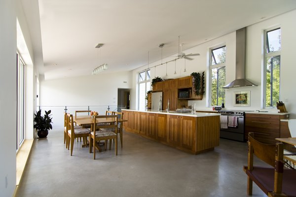 Modern home with kitchen, wood cabinet, concrete floor, ceiling lighting, track lighting, refrigerator, range hood, range, and wall oven. Gananoque Lake Road House - Great Room Photo 3 of Gananoque Lake Road House