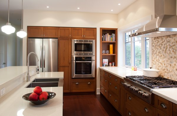 Modern home with kitchen, wood cabinet, ceiling lighting, pendant lighting, refrigerator, wall oven, cooktops, range hood, and microwave. Black Creek Ravine - Kitchen Photo 6 of Black Creek Ravine