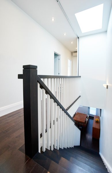 Modern home with staircase, wood tread, and wood railing. Pape Village House - Stairs Photo  of Pape Village
