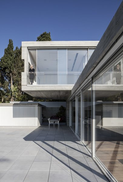 These two shapes extend over a horizontal axis. Some parts are overlapping while in other areas they detach and break out in opposite directions. The upper volume functions as the private spaces, while the lower volume functions as the public spaces.  Photo 3 of The Dual House modern home