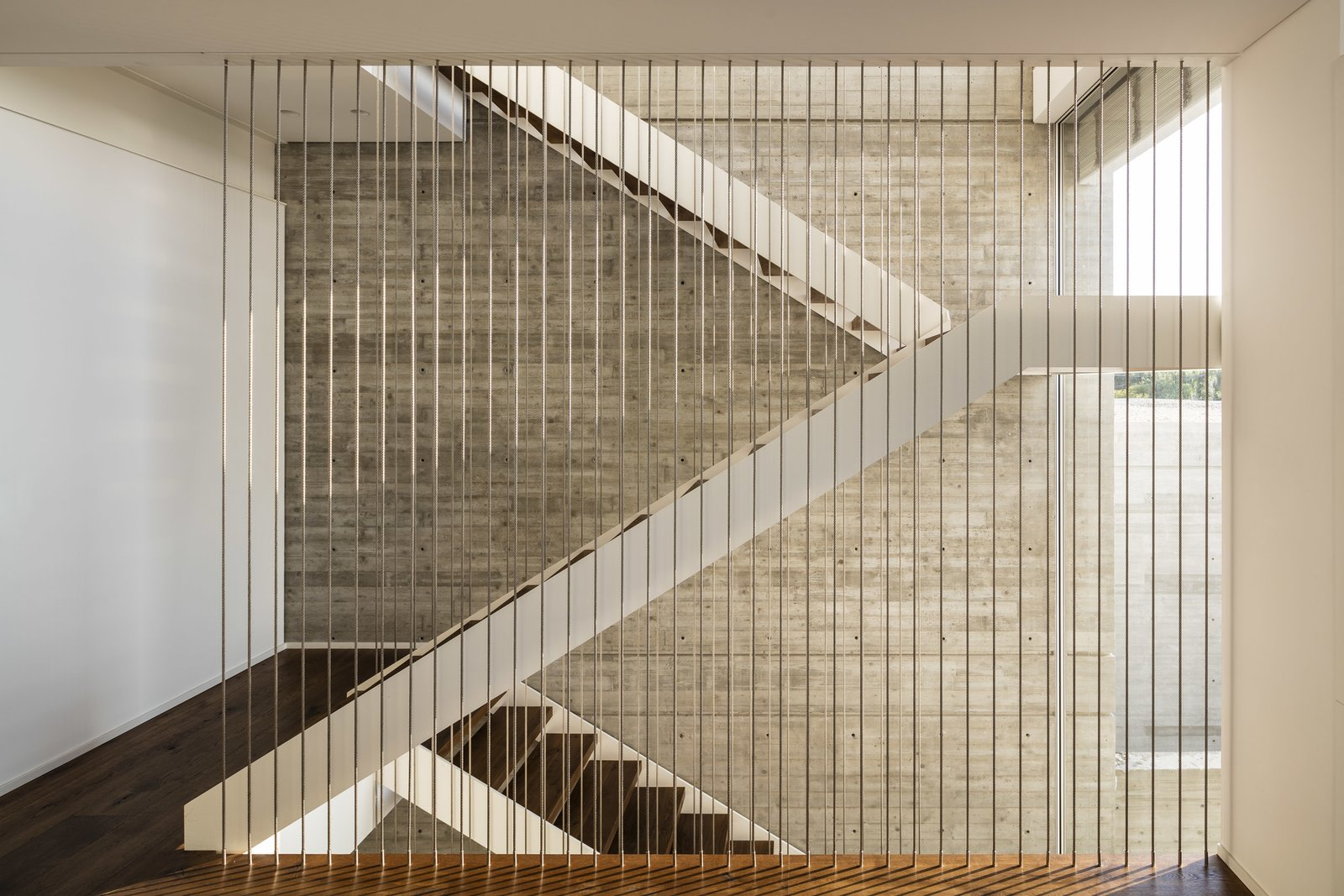 At the meeting point of these two masses, public and private spaces, is a vertical axis that cuts the horizontal plane with the use of a staircase that goes through all levels of the house.
