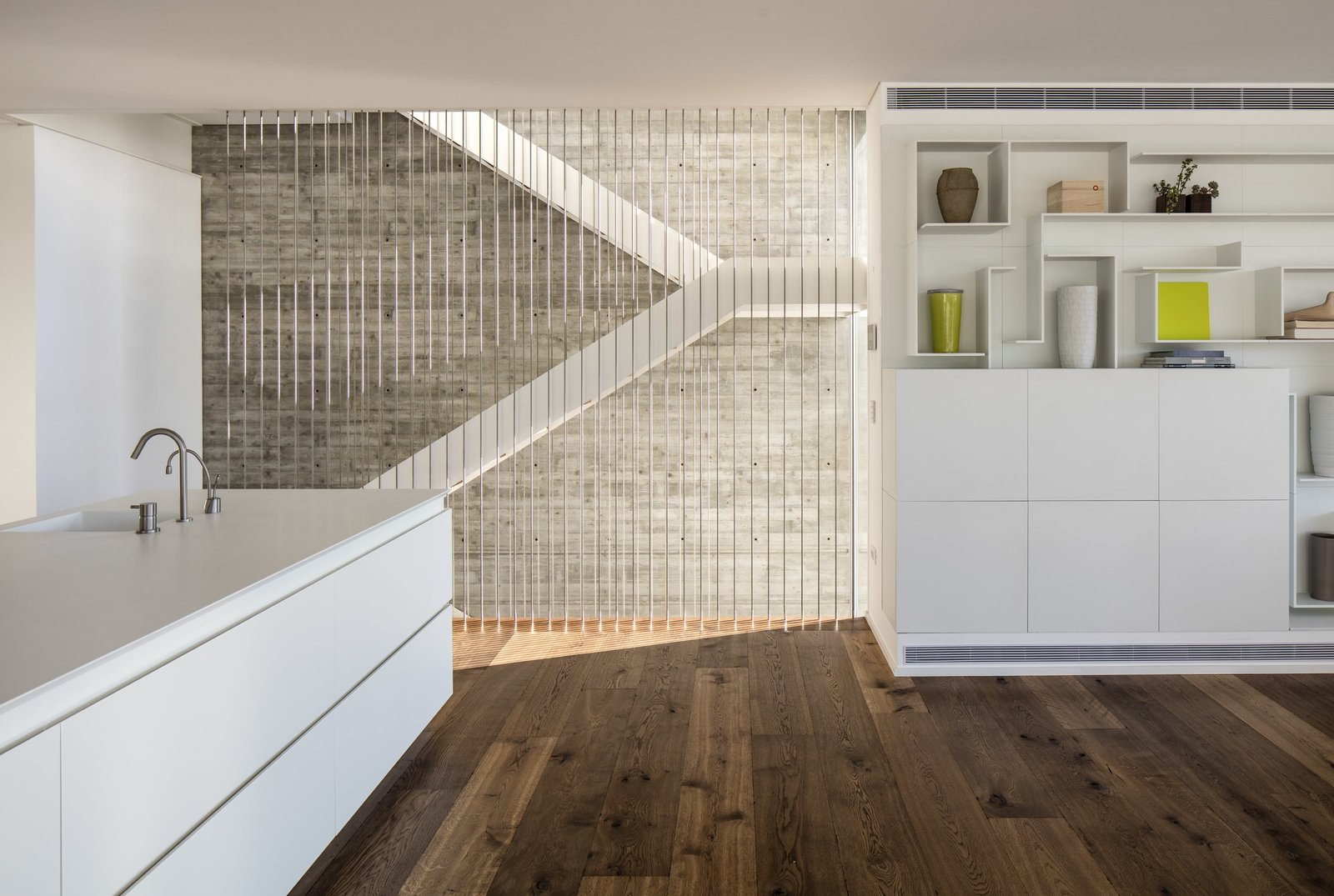 The staircase goes through the center of the house, pictured here adjacent to the open plan kitchen/living area.