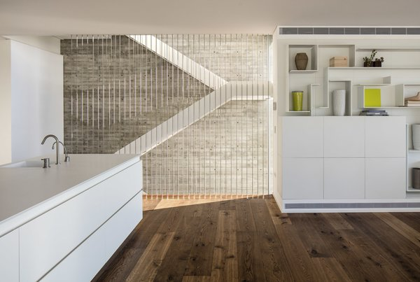 The staircase goes through the center of the house, pictured here adjacent to the open plan kitchen/living area. Photo 7 of The Dual House modern home
