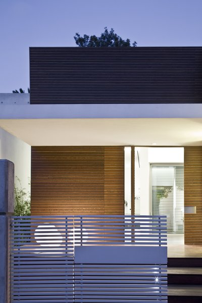 A dramatic front entrance comprised of horizontal wooden slats and a cantilevered canopy. Photo 11 of eHouse modern home