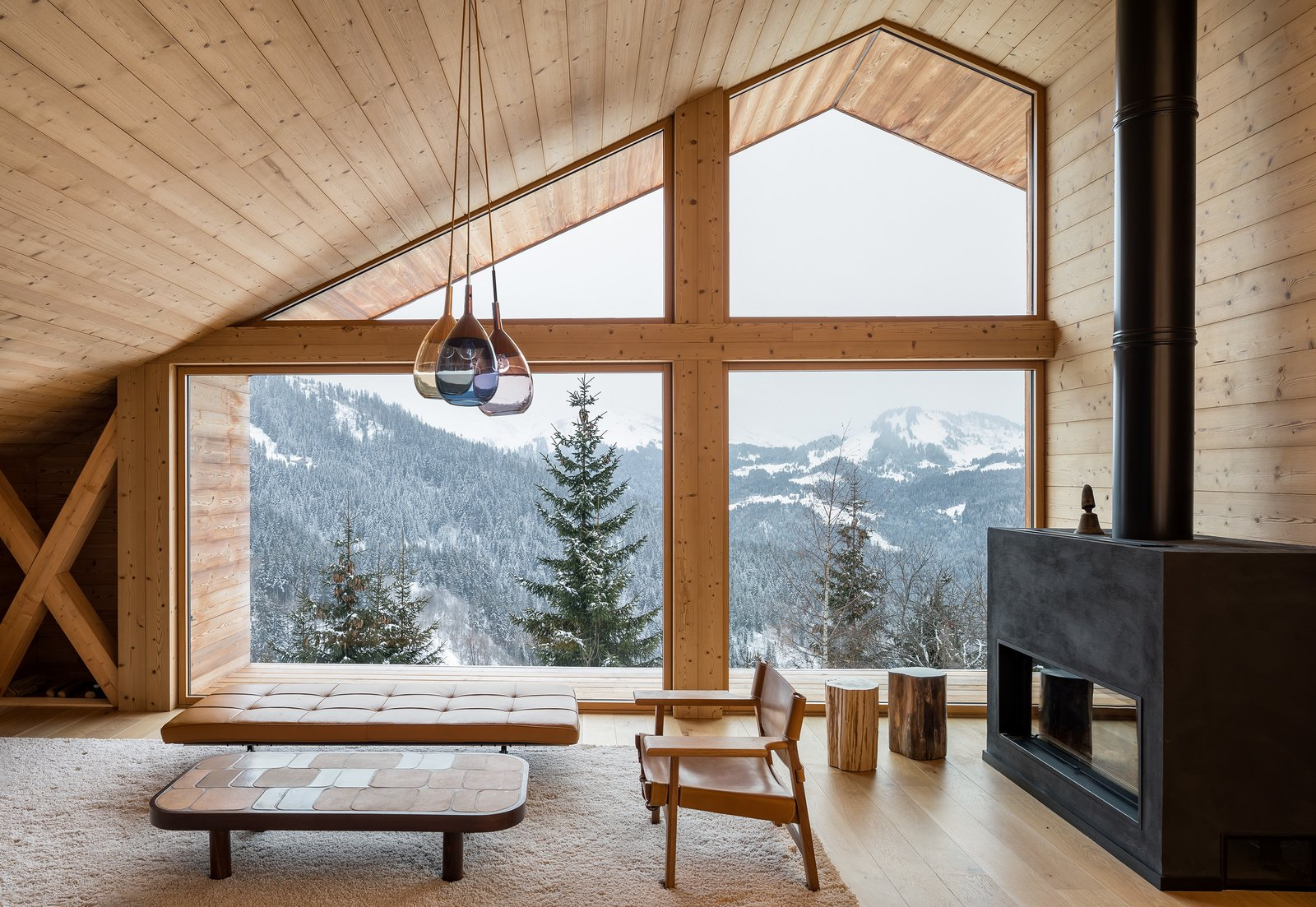 Tagged: Living Room, Ottomans, End Tables, Coffee Tables, Wood Burning Fireplace, Ceiling Lighting, and Light Hardwood Floor.  Mountain House by studio razavi architecture