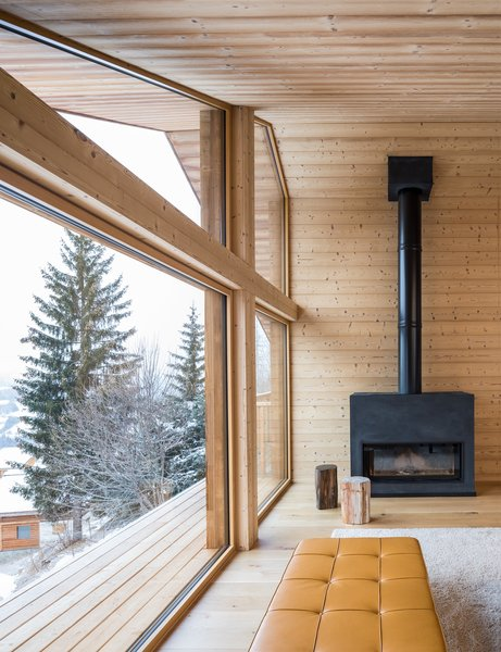 Modern home with living room, ottomans, console tables, coffee tables, light hardwood floor, and wood burning fireplace. Photo 12 of Mountain House