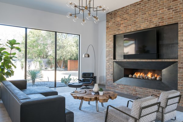 Metal and brick fireplace with cement balls.  Eames chair and cut root wood coffee table.  Italian leather sofa and cut velvet chairs from Cantoni.  Photo 5 of Industrial Modern Home built by husband and wife team modern home