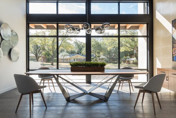 Wall of windows in this modern dining room.  Walnut and iron table with walnut buffet.  Photo 7 of Industrial Modern Home built by husband and wife team modern home