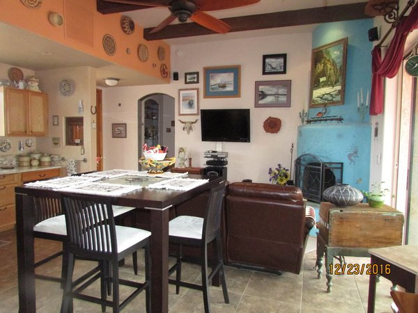 Great Room with wood burning fireplace all tile, granite countertop kitchen... Photo  of Caliente Creek Ranch modern home