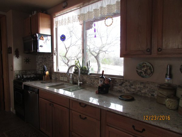 Kitchen area with gas stove, granite counters, dishwasher and huge window to see all the critters Photo 2 of Caliente Creek Ranch modern home
