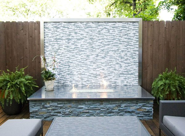 A custom firepit with glass tile, stainless steel counter and stacked stone bring the focus to this patio area.   Photo  of Outdoor Living modern home