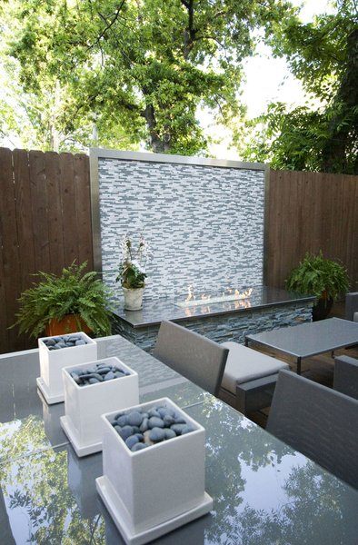 A custom firepit with glass tile, stainless steel counter and stacked stone bring the focus to this patio area.  Cooking, dining and seating areas were created to allow for zones when entertaining. Photo 2 of Outdoor Living modern home
