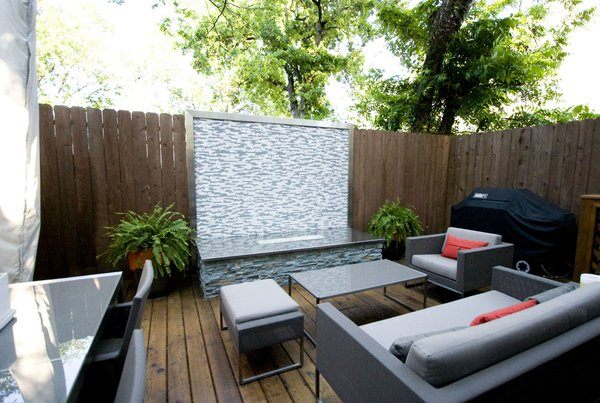 A custom firepit with glass tile, stainless steel counter and stacked stone bring the focus to this patio area.  Cooking, dining and seating areas were created to allow for zones when entertaining. Photo 3 of Outdoor Living modern home