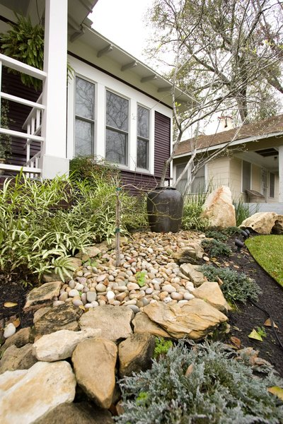 Boulders, a water feature and a river path were created in the front yard to enhance the asian flair this home had.  Landscape lighting was installed to ensure that the home felt warm even at night. Photo 10 of Asian Bungalow modern home