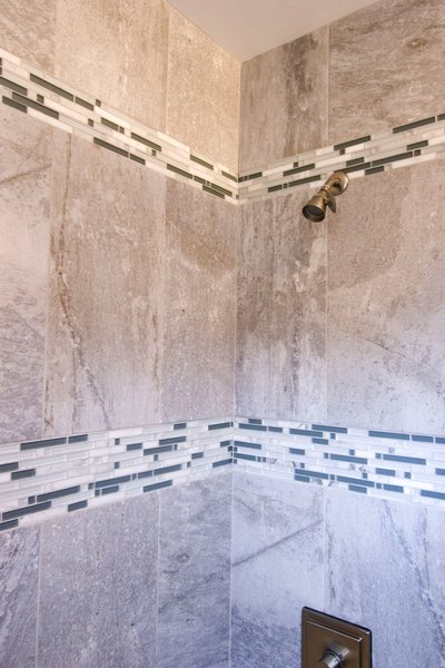 The bathroom was updated with modern finishes, while tile was used in a unique banding stripe to provide interest while saving money. Photo 9 of Asian Bungalow - Garden Apartment modern home