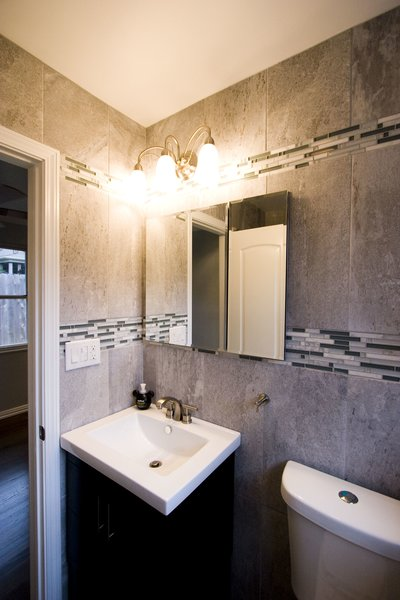 The bathroom was updated with modern finishes, while tile was used in a unique banding stripe to provide interest while saving money. Photo 8 of Asian Bungalow - Garden Apartment modern home