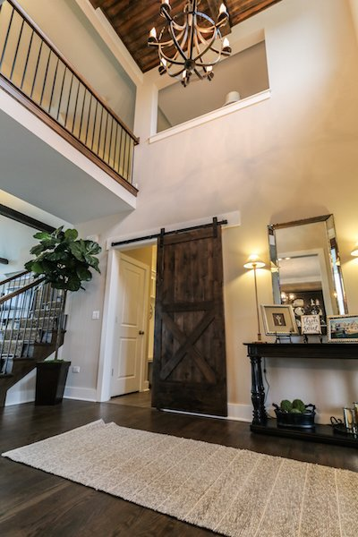 Dramatic two story foyer with stained coffered ceiling detail and barn sliding door Photo 10 of Modified Amelia II Model by DJK Homes modern home
