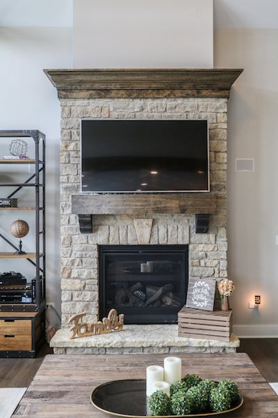 Custom stone fireplace with custom wood beam mantle located in great room Photo 11 of Modified Amelia II Model by DJK Homes modern home