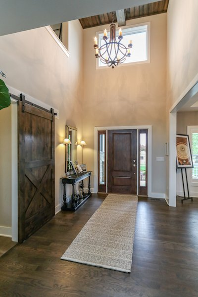 Dramatic two story foyer with coffered ceiling detail and barn sliding door Photo 13 of Modified Amelia II Model by DJK Homes modern home