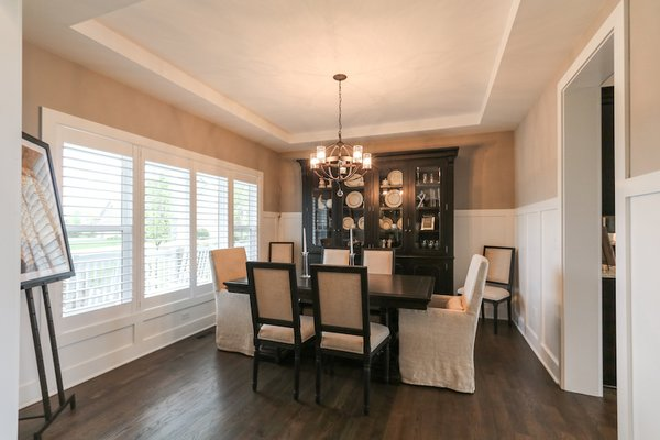 Elegant dining room with custom wainscoting and stepped ceiling detail  Photo 14 of Modified Amelia II Model by DJK Homes modern home