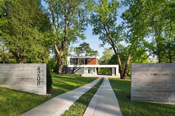 A board formed concrete wall provides a threshold at the arrival and frames a view of the house Photo 16 of Boetger Residence modern home