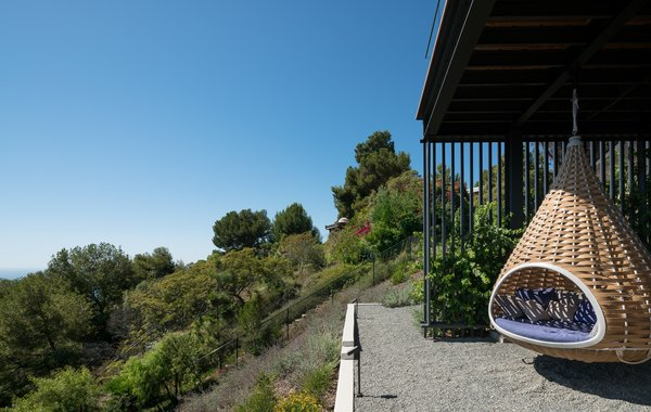 Modern home with outdoor, decomposed granite patio, porch, deck, slope, trees, and shrubs. Swing suspended below terrace Photo 9 of Malibu Hillside