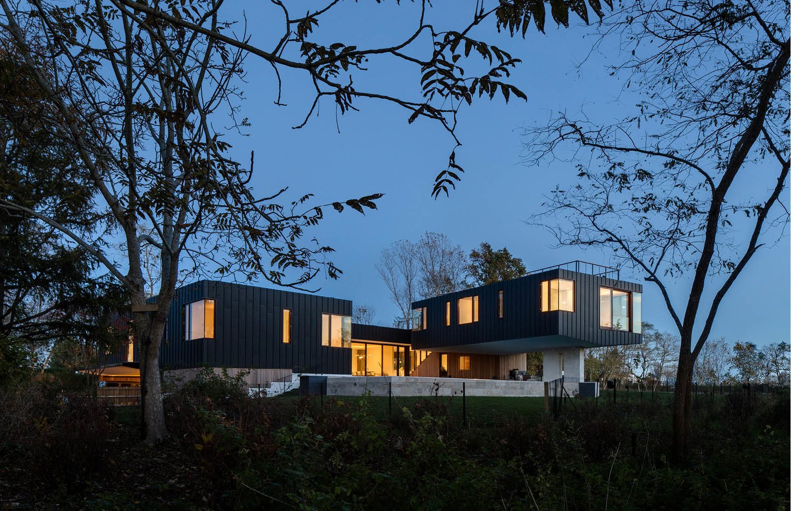 Rear of the house at dusk. Watermill House by Office of Architecture