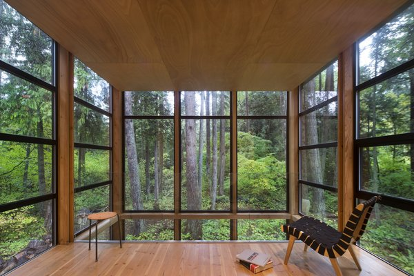 The feeling of being enveloped in the forest is heightened by windows that extend a couple of inches above the slightly dropped hemlock ceiling. This space was originally going to contain the master bedroom until the Owner realized that the view—and the feeling of being in a treehouse—was too magical to waste on a room used for sleeping. Photo 8 of Lightbox modern home