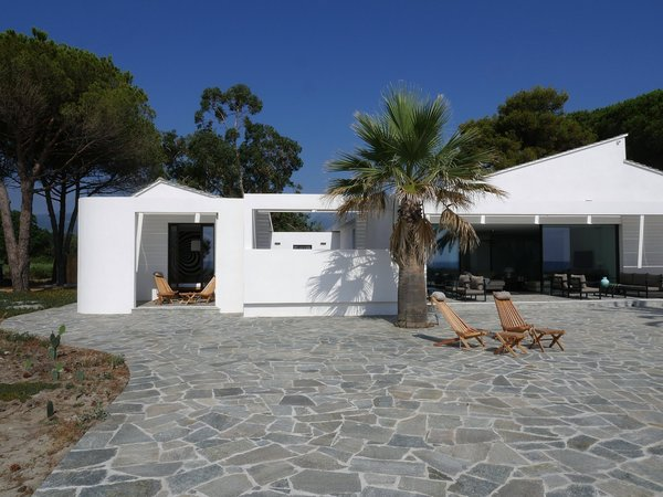 Located steps from the beaches of Corsica, this striking modern beach house was designed by Paris-based architect Vincent Leprince, as a bright and bold reference to the sunshine-washed coastal surroundings. It features living room doors that open onto a terrace with panoramic views, and that leads directly to the beach. The home is tastefully decorated with contemporary furnishings and includes a heated spa with views of the island of Monte Cristo.
