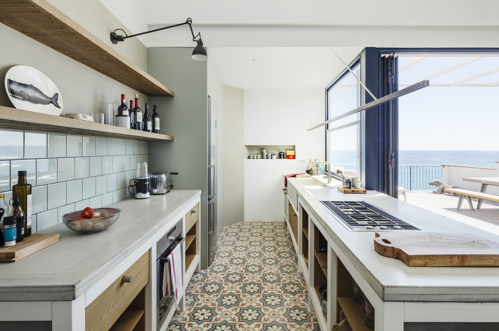Tagged: Kitchen, Concrete Counter, Ceramic Tile Floor, Refrigerator, Wall Oven, Porcelain Tile Backsplashe, Wall Lighting, Range, and Drop In Sink.  Photo 8 of 16 in A Careful Renovation Brings New Life to a Family's Heritage Home on the Spanish Coast