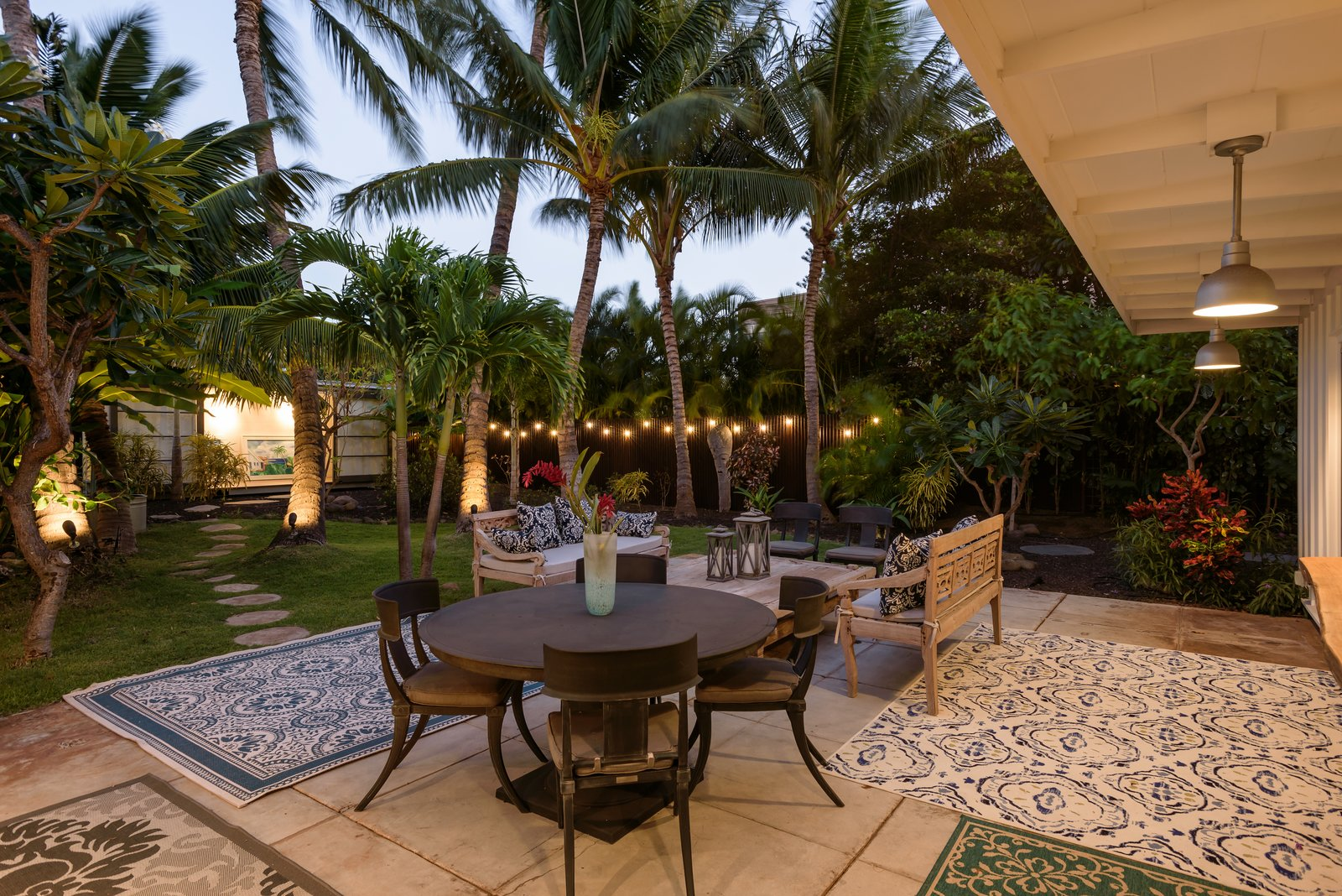 Tagged: Outdoor, Trees, Back Yard, Large Patio, Porch, Deck, Hanging Lighting, Shrubs, Grass, and Walkways.  Photo 9 of 13 in A Renovated Hawaiian Beach House From the 1950s Asks $1.79M