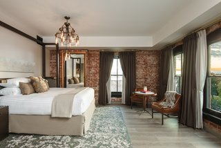 This Group Is Reimagining the Future of Boutique Hotels - Photo 8 of 14 - Guests can enjoy plush, comfortable bedding in each room, along with exquisite exposed brick.