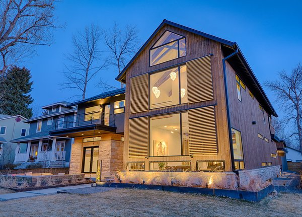 Barn rail system with moveable shutters which provide cover for large south facing windows. Elegant pine cone shaped lighting creates art and glow. Photo  of Modern Barn Revival modern home