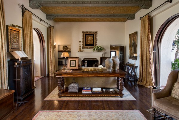 The main house showcases a great room with original gold-leaf ceiling panels and arched mahogany pocket doors, opening the entire home to the gardens and fountains. Photo 7 of Casa Comodoro modern home