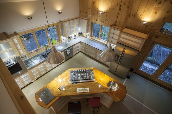 The hand built maple kitchen with walnut and mahogany island. The floor is poured concrete with radiant heating beneath. Photo 2 of The Bath House modern home