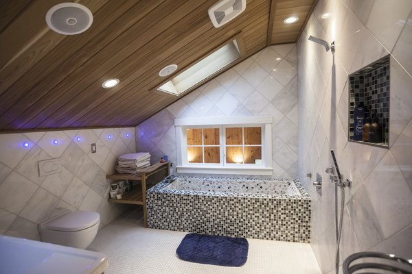 Upstairs the combined wet room and bathroom includes a hand built six feet long soaking tub with a river stone surface. The ceiling is cedar wood. Photo 4 of The Bath House modern home