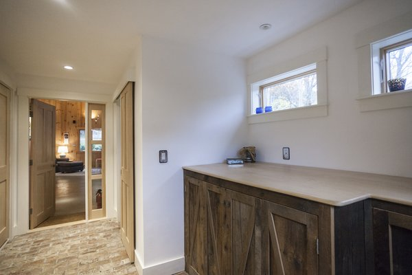 The bricks in the underfloor heated hallway came from an old chimney previously attached to the back of the building which had to be dismantled. Old barn board and new maple are used in partnership for the doors. Photo 5 of The Bath House modern home