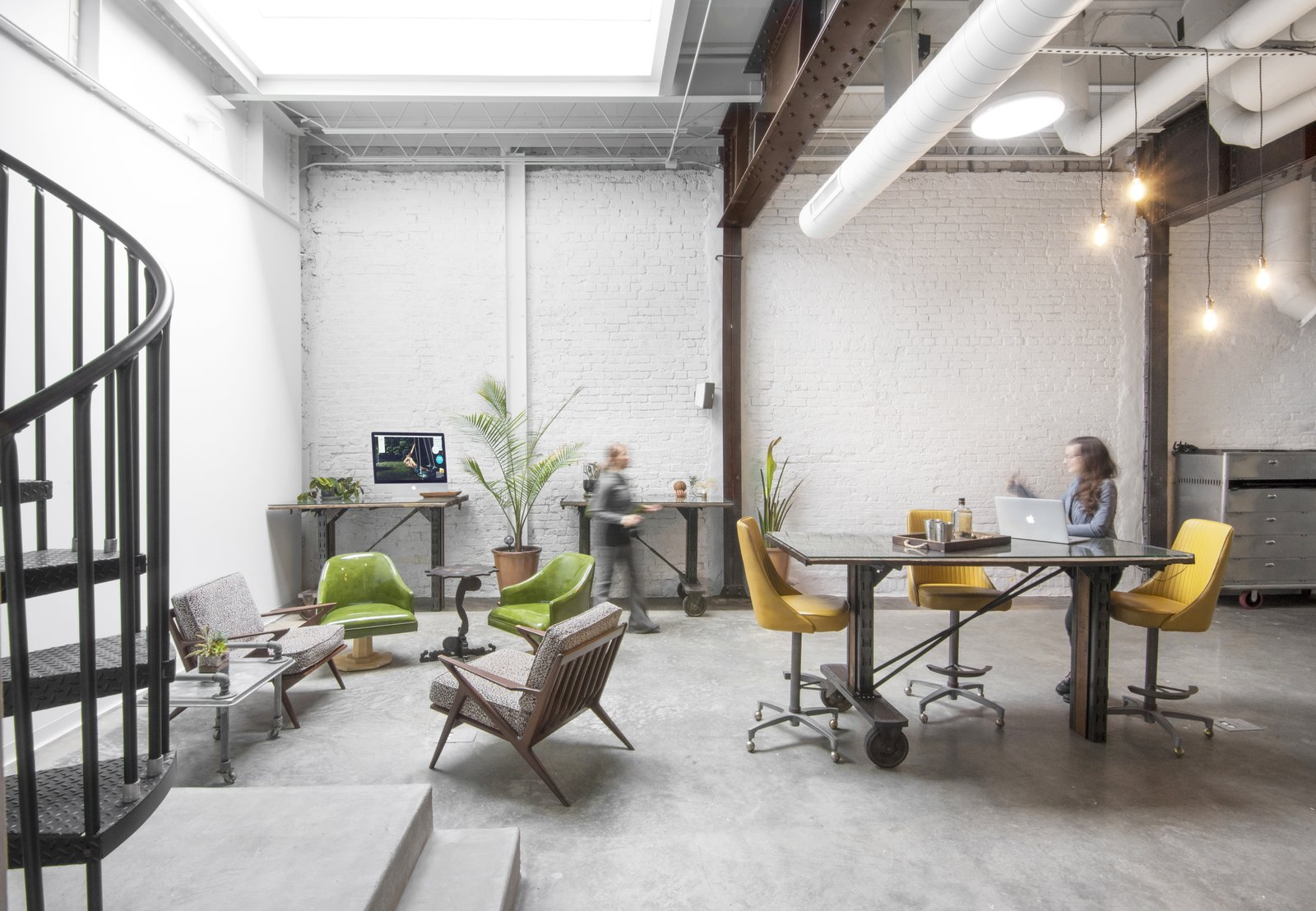 Studio work space featuring standing desks made from up cycled RR carts, giant skylight. Studio GoodLight by Liesa Cole