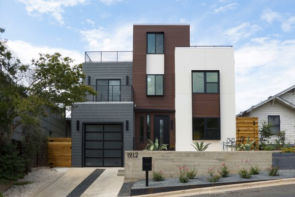 Modern home with outdoor, front yard, slope, flowers, raised planters, concrete patio, porch, deck, hardscapes, wood fence, and metal patio, porch, deck. Exterior View from Street Photo  of East 9th House